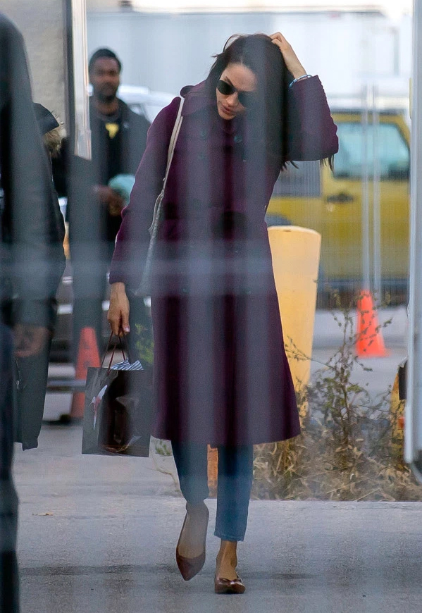 Meghan Markle on the set of Suits in Toronto, Canada, wearing a Sentaler Double Breasted Trench Coat in Mulberry, carrying a Goyard tote and Sarah Flint Natalie Flats on November 14, 2016.